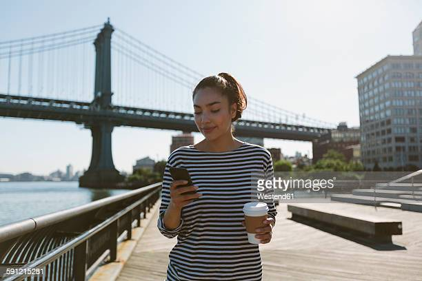 USA, New York City, portrait of smiling young woman with coffee to go looking at her smartphone