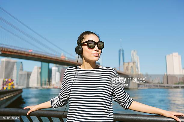 USA, New York City, portrait of young woman with headphones and sunglasses in front of skyline
