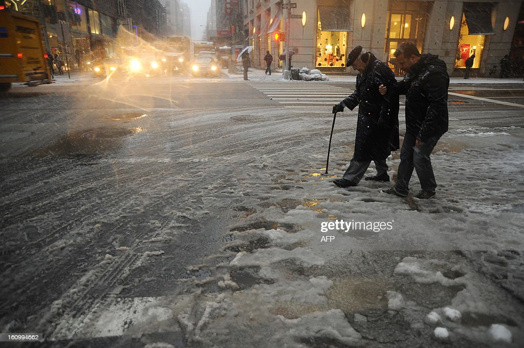 New York City residents cross a street covered in slush on February 8, 2013 during a storm affecting the northeast US. The storm was forecast to bring the heaviest snow to the densely-populated northeast corridor so far this winter, threatening power and transport links for tens of millions of people and the major cities of Boston and New York. New York and other regional airports saw more than 4,500 cancellations ahead of what the National Weather Service called 'a major winter storm with blizzard conditions' along most of the region's coastline.