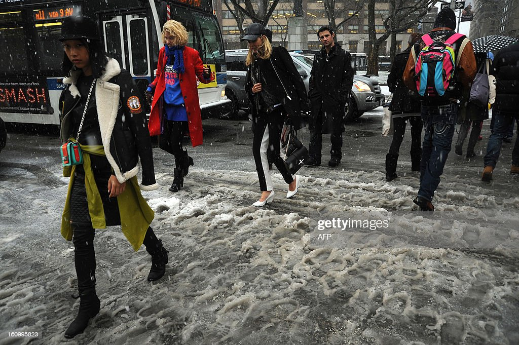 New York City residents cross a street covered in slush on February 8, 2013 during a storm affecting the northeast US. The storm was forecast to bring the heaviest snow to the densely-populated northeast corridor so far this winter, threatening power and transport links for tens of millions of people and the major cities of Boston and New York. New York and other regional airports saw more than 4,500 cancellations ahead of what the National Weather Service called 'a major winter storm with blizzard conditions' along most of the region's coastline. AFP PHOTO / MEHDI TAAMALLAH