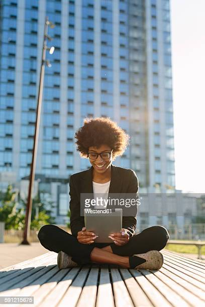 USA, New York City, smiling businesswoman sitting on a bench using digital tablet