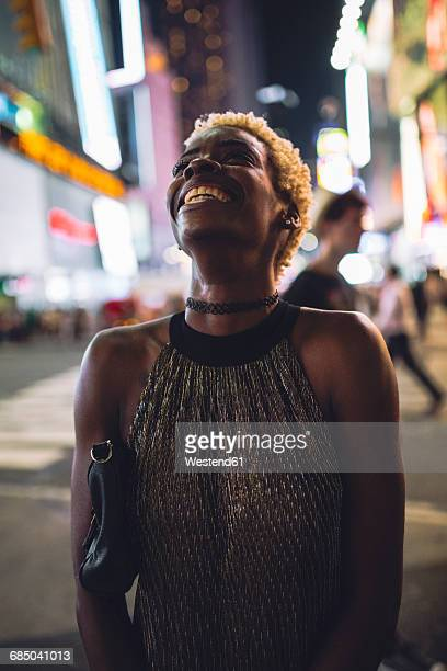 USA, New York City, smiling young woman on Times Square at night looking up