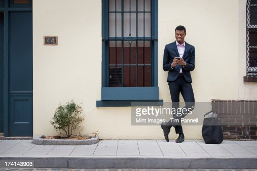 New York city street life. Young people outdoors on the city streets in springtime.  A man leaning against a wall.