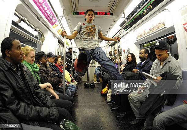 New York City Subway dancer Marcus Walden aka Mr Wiggles performs acrobatic tricks on the subway while passengers watch November 23 2010 The dance...