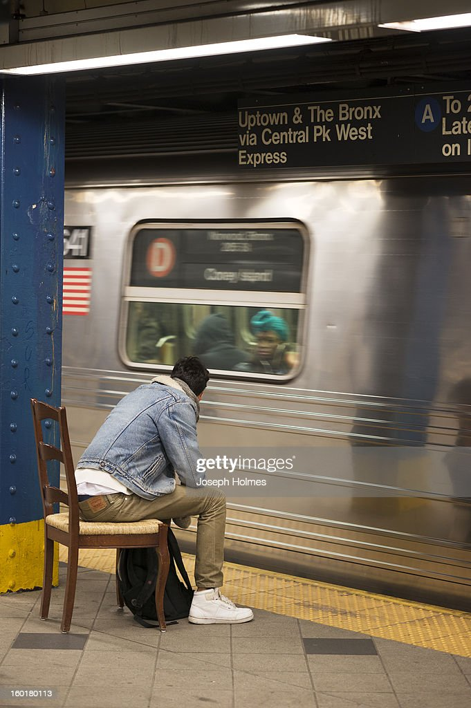 New York City subway passenger sits on a chair watching an arriving D train on a subway platform.