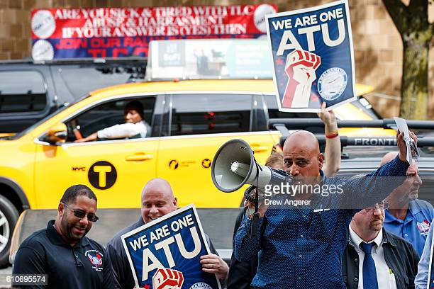 New York City taxi cab drives by as Syed Manzar who drives for both Uber and Lyft speaks during a rally to call on the New York City Taxi and...