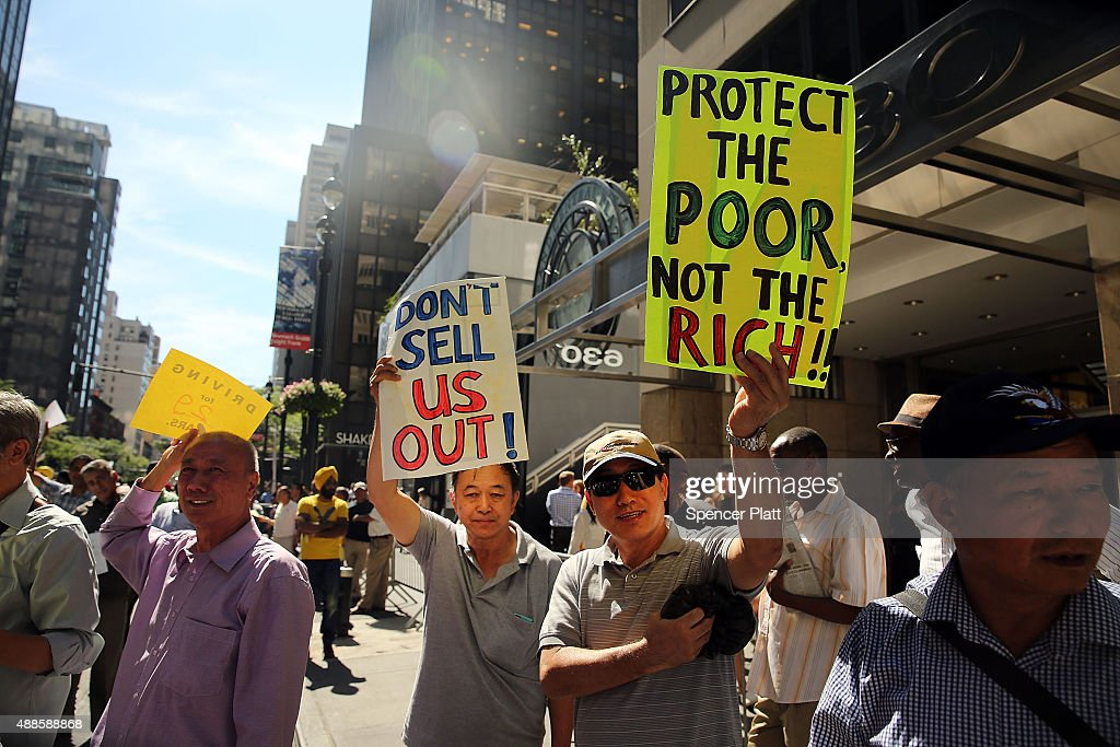 New York City taxi drivers hold a rally in front of Governor Andrew Cuomo's office to protest against recent inroads made by the Uber car service on September 16, 2015 in New York City. Calling Uber's business model dangerous to worker's full time employment, the drivers joined with the New York Taxi Workers Alliance in demanding that the state begin to regulate private car services.