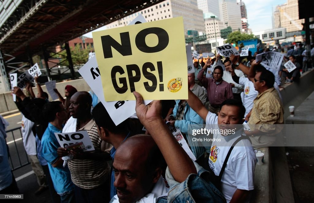 New York City taxi drivers hold signs aloft during a protest October 22, 2007 in New York. Some taxi drivers in New York are on strike, protesting a plan by the NYC Taxi & Limousine Commission to install GPS trackers and credit card machines in New York yellow cabs.