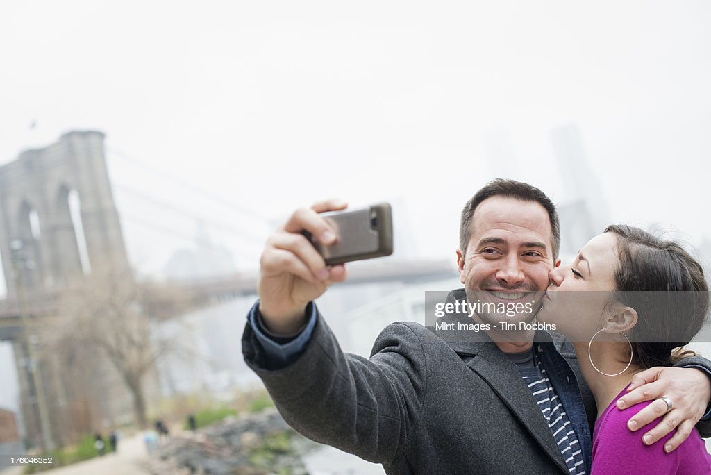New York city. The Brooklyn Bridge crossing over the East River. A couple taking a picture with a phone, a selfy of themselves. : Stock Photo