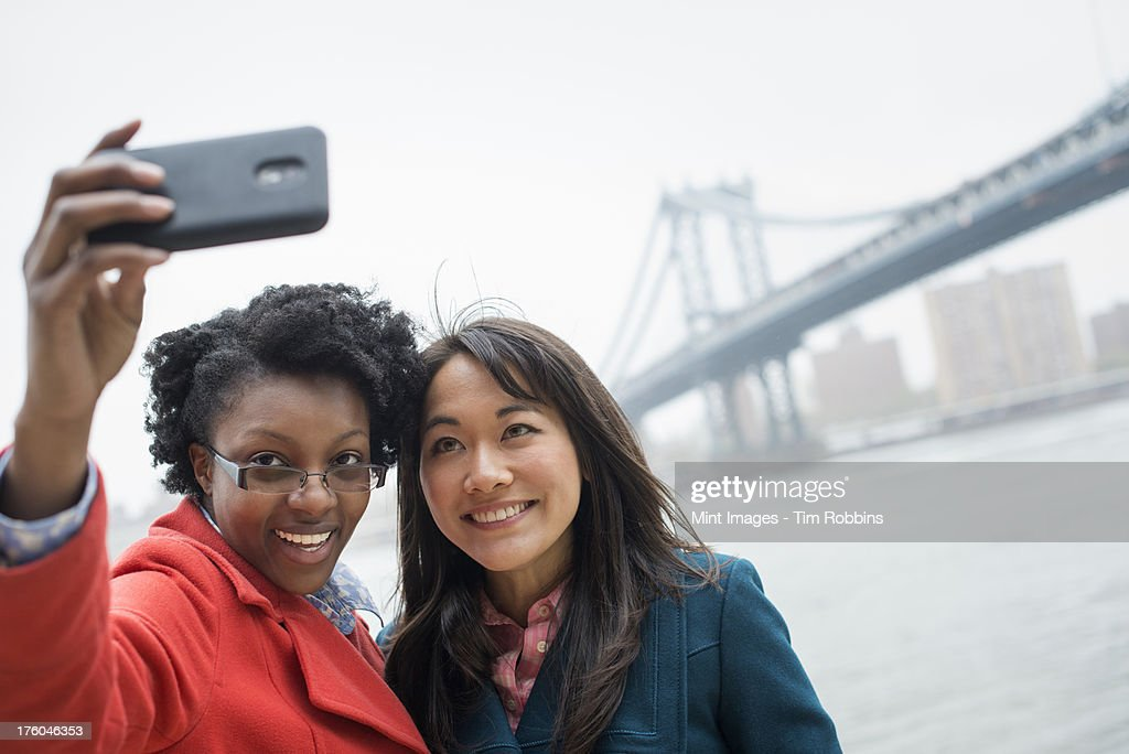 New York city. The Brooklyn Bridge crossing over the East River. A couple, two women, taking a picture with a phone, a selfy of themselves. : Stock Photo