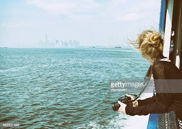USA, New York City, Tourist with camera on Staten Island Ferry with view of Manhattan skyline and East River