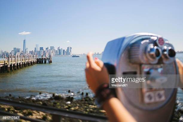 USA, New York City, view to the skyline with person using coin operated binoculars in the foreground
