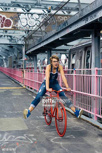 USA, New York City, Williamsburg, woman with red racing cycle on Williamsburg Bridge