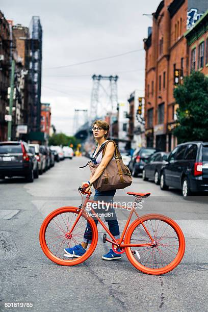 USA, New York City, Williamsburg, woman withg red racing cycle crossing the street