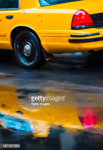USA, New York City, Yellow cab reflecting in rain puddle : Stock Photo