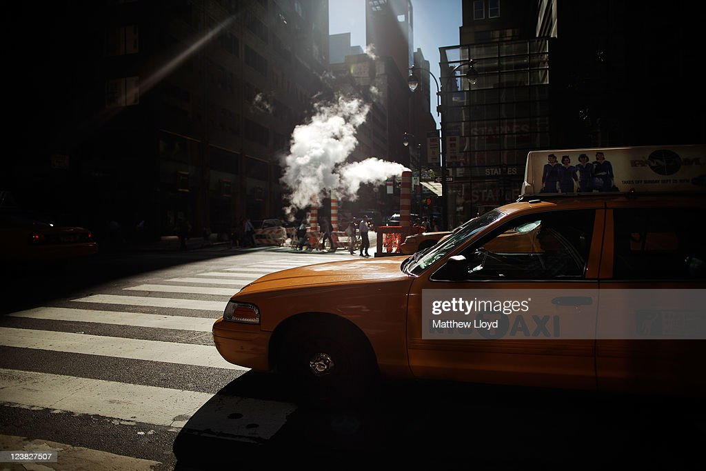 New York City yellow taxis travel past steam rising from vents on August 22, 2011 in New York City. New York City, a financial, cultural and tourism centre, has the largest population of any city in the United States.