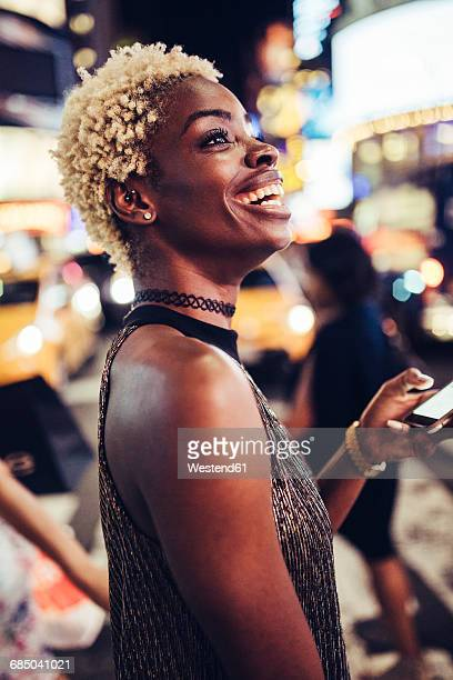 USA, New York City, young woman on Times Square at night watching something