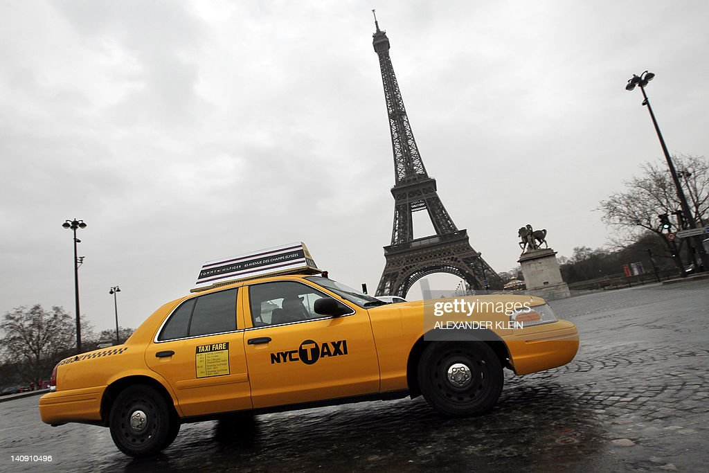 A New York City's legendary yellow taxi car passes in front of the famous Eiffel Tower, in Paris, on March 7, 2012.