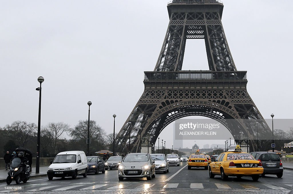 New York City's legendary yellow taxi cars (R) pass next to the famous Eiffel Tower, in Paris, on March 7, 2012.