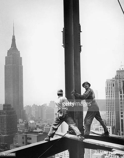 New York construction workers circa 1950 The Empire State Building towers in the background