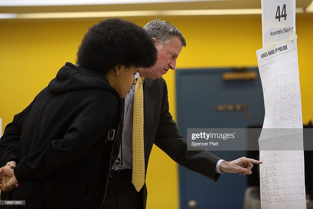 New York Democratic mayoral candidate Bill de Blasio (R) stands with his son Dante de Blasio as he prepares to vote at his local precinct at a public library branch on Election Day on November 5, 2013 in the Brooklyn borough of New York City. De Blasio holds a significant lead in the polls over his challenger Republican mayoral candidate Joe Lhota.