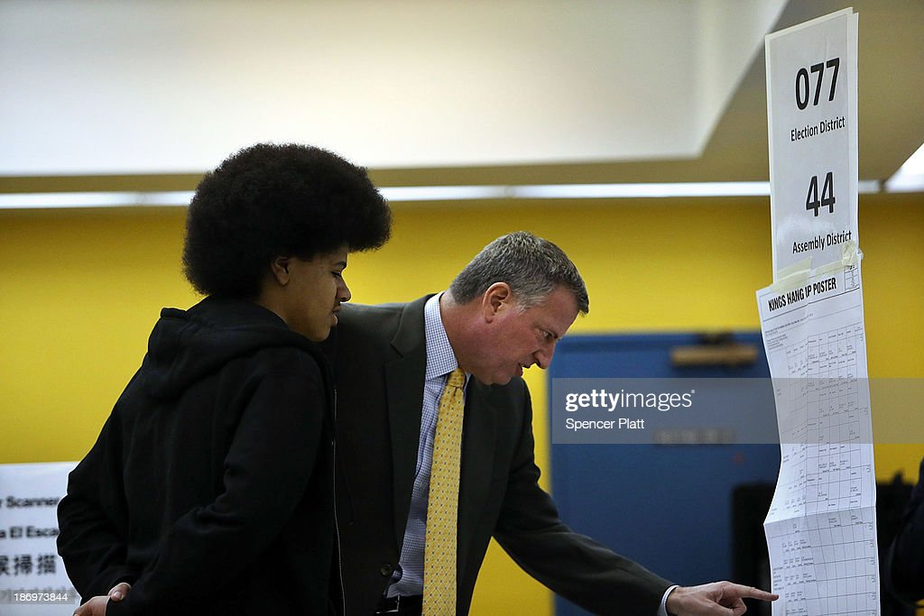 New York Democratic mayoral candidate <a gi-track='captionPersonalityLinkClicked' href=/galleries/search?phrase=Bill+de+Blasio&family=editorial&specificpeople=6224514 ng-click='$event.stopPropagation()'>Bill de Blasio</a> (R) stands with his son Dante de Blasio as he prepares to vote at his local precinct at a public library branch on Election Day on November 5, 2013 in the Brooklyn borough of New York City. De Blasio holds a significant lead in the polls over his challenger Republican mayoral candidate Joe Lhota.