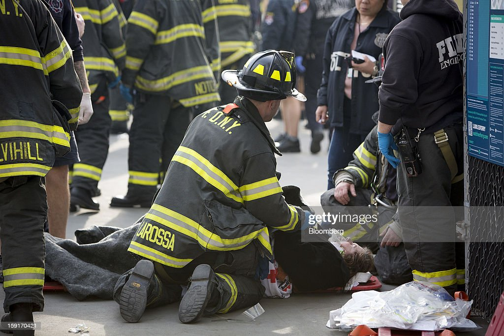 A New York Fire Department (NYFD) firefighter tends to an injured ferry commuter on a stretcher in New York, U.S., on Wednesday, Jan. 9, 2013. A Seastreak commuter ferry crashed into a pier near Lower Manhattan's financial district during the morning rush hour, injuring dozens, including two critically, police said. Photographer: Scott Eells/Bloomberg via Getty Images