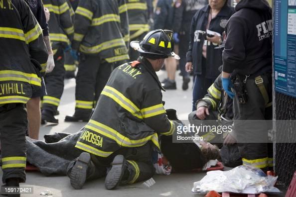 A New York Fire Department firefighter tends to an injured ferry commuter on a stretcher in New York US on Wednesday Jan 9 2013 A Seastreak commuter...