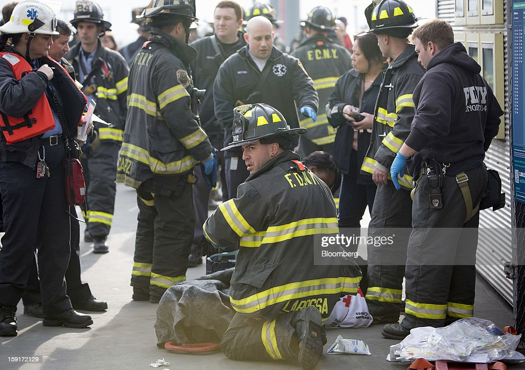 A New York Fire Department (NYFD) firefighter tends to an injured ferry commuter on a stretcher in New York, U.S., on Wednesday, Jan. 9, 2013. A Seastreak Wall Street commuter ferry crashed into a pier near Lower Manhattan's financial district during the morning rush hour, injuring dozens, including two critically, police said. Photographer: Scott Eells/Bloomberg via Getty Images
