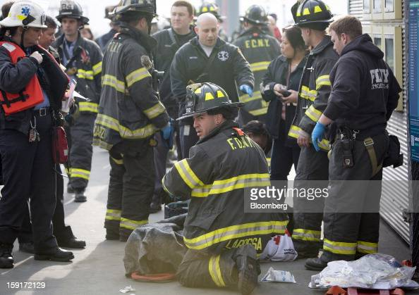 A New York Fire Department firefighter tends to an injured ferry commuter on a stretcher in New York US on Wednesday Jan 9 2013 A Seastreak Wall...
