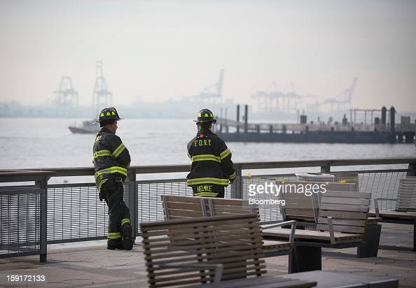 New York Fire Department firefighters look at the scene of a ferry accident at Pier 11 in New York US on Wednesday Jan 9 2013 Seastreak Wall Street...