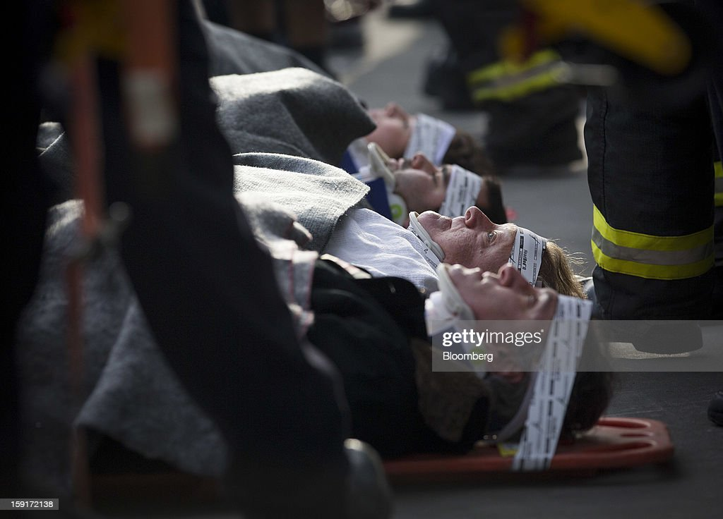 New York Fire Department (NYFD) firefighters prepare to take away injured ferry commuters on stretchers in New York, U.S., on Wednesday, Jan. 9, 2013. A Seastreak Wall Street commuter ferry crashed into a pier near Lower Manhattan's financial district during the morning rush hour, injuring dozens, including two critically, police said. Photographer: Scott Eells/Bloomberg via Getty Images