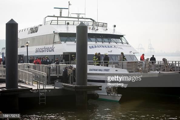 New York Fire Department firefighters stand above damage on a Seastreak commuter ferry in New York US on Wednesday Jan 9 2013 A Seastreak commuter...
