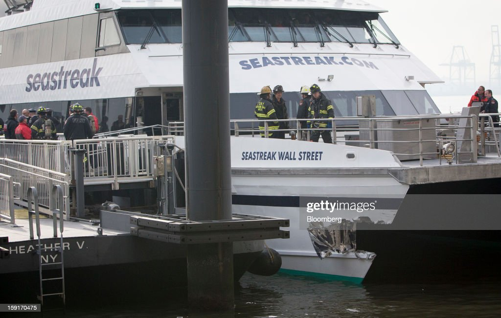 New York Fire Department (NYFD) firefighters stand above damage on a Seastreak Wall Street commuter ferry in New York, U.S., on Wednesday, Jan. 9, 2013. A Seastreak Wall Street commuter ferry crashed into a pier near Lower Manhattan's financial district during the morning rush hour, injuring dozens, including two critically, police said. Photographer: Scott Eells/Bloomberg via Getty Images