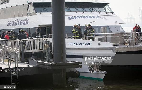 New York Fire Department firefighters stand above damage on a Seastreak Wall Street commuter ferry in New York US on Wednesday Jan 9 2013 A Seastreak...