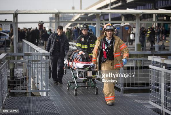 New York Fire Department firefighters take away an injured ferry commuter on a stretcher in New York US on Wednesday Jan 9 2013 A Seastreak commuter...