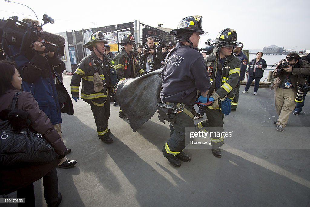 New York Fire Department (NYFD) firefighters take away an injured ferry commuter on a stretcher in New York, U.S., on Wednesday, Jan. 9, 2013. A Seastreak commuter ferry crashed into a pier near Lower Manhattan's financial district during the morning rush hour, injuring dozens, including two critically, police said. Photographer: Scott Eells/Bloomberg via Getty Images