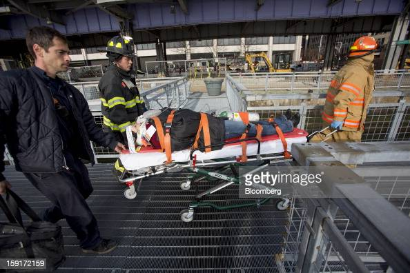 New York Fire Department firefighters take away an injured ferry commuter on a stretcher in New York US on Wednesday Jan 9 2013 A Seastreak Wall...