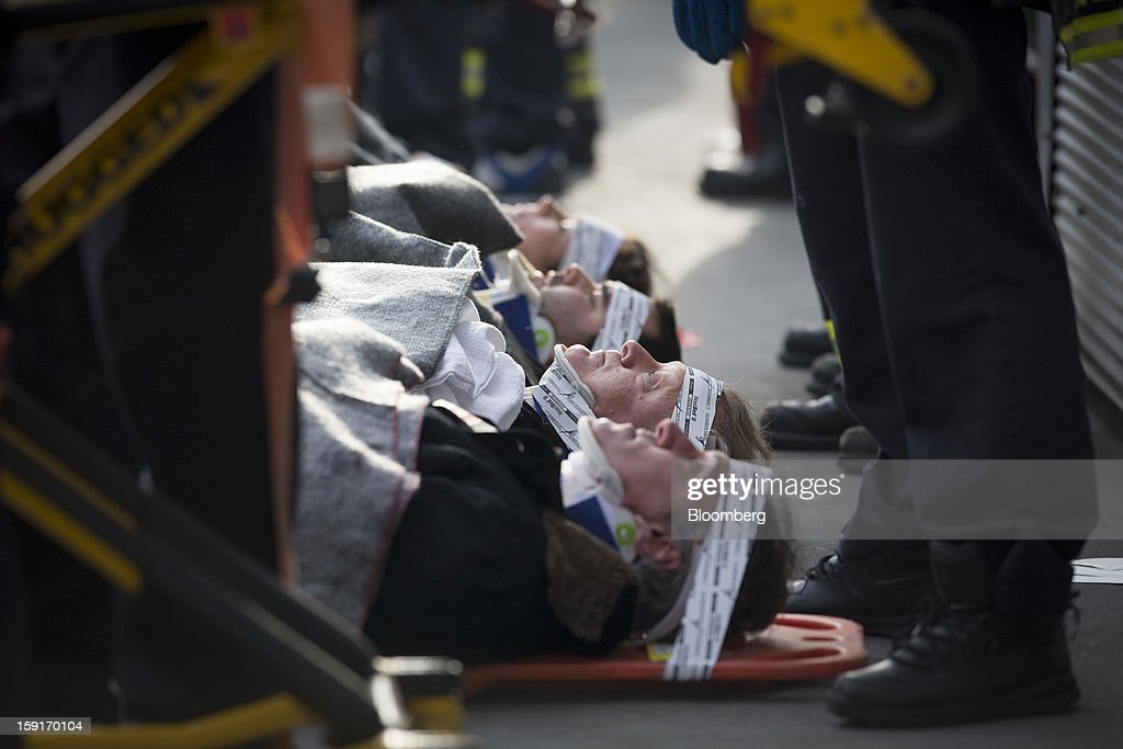 New York Fire Department (NYFD) firefighters take away injured ferry commuters on stretchers in New York, U.S., on Wednesday, Jan. 9, 2013. A Seastreak commuter ferry crashed into a pier near Lower Manhattan's financial district during the morning rush hour, injuring dozens, including two critically, police said. Photographer: Scott Eells/Bloomberg via Getty Images