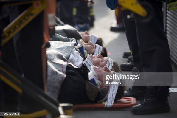 New York Fire Department firefighters take away injured ferry commuters on stretchers in New York US on Wednesday Jan 9 2013 A Seastreak commuter...