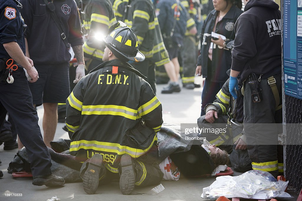 New York Fire Department (NYFD) firefighters tend to injured ferry commuters on stretchers in New York, U.S., on Wednesday, Jan. 9, 2013. A Seastreak commuter ferry crashed into a pier near Lower Manhattan's financial district during the morning rush hour, injuring dozens, including two critically, police said. Photographer: Scott Eells/Bloomberg via Getty Images
