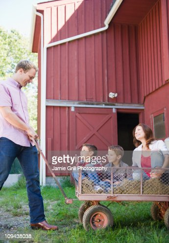 USA, New York, Flanders, Father pulling mother and two boys (4-5, 8-9) on trolley