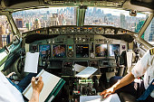 Flight in airplane cabin interior on New York skyline of United States of America.. Pilots arms and blank white papers for copy space