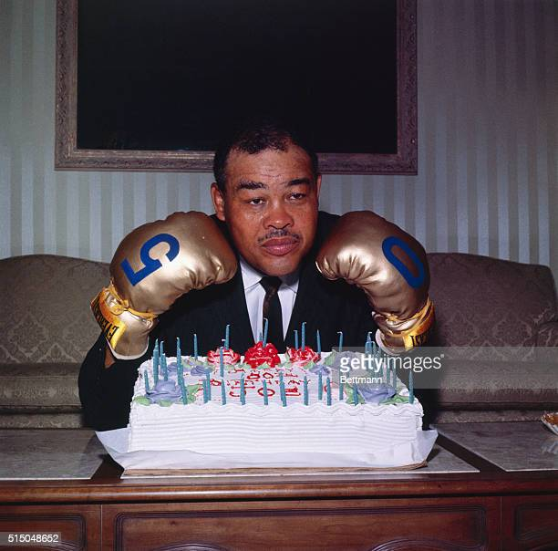 Former world heavyweight boxing champion Joe Louis displays gloves with the numerals five and zero painted on them as he prepares to celebrate his...