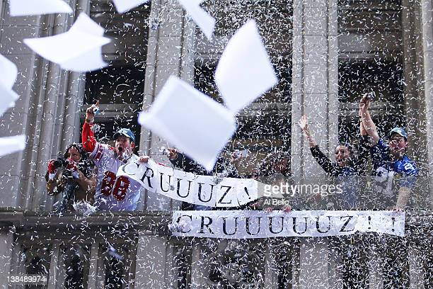 New York Giants fans hold a Victor Cruz sign as ticker tape drops during the New York Giants ticker tape victory parade down the Canyon of Heros on...