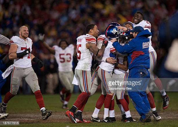 New York Giants field goal kicker Lawrence Tynes is mobbed by teammates after kicking the winning field goal against the San Francisco 49ers in the...