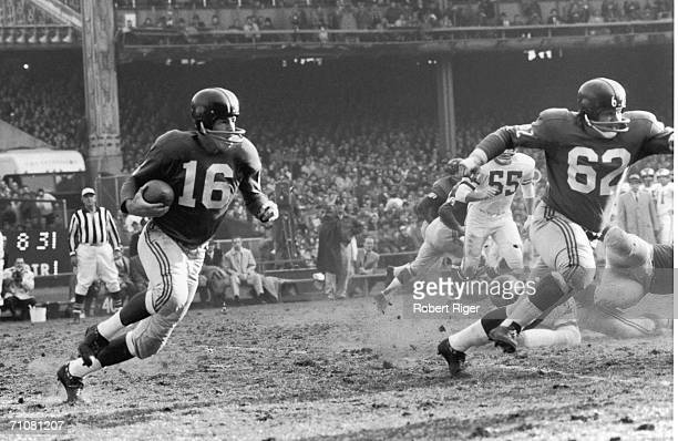 New York Giants football player Frank Gifford runs with protection from teammate Darrell Dess during a game against the Philadelphia Eagles 1960s
