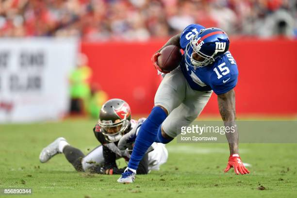 New York Giants wide receiver Brandon Marshall tries to keep his balance as he breaks through a tackle during an NFL football game between the New...