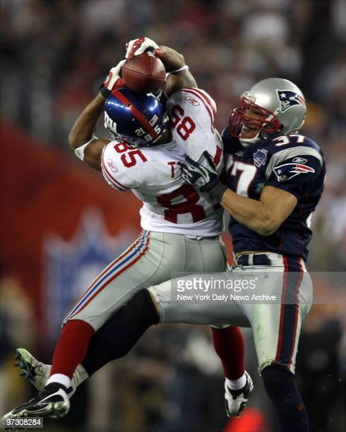 New York Giants' wide receiver David Tyree pins the ball to his helmet as he catches a 32yard pass late in the fourth quarter of Super Bowl XLII...
