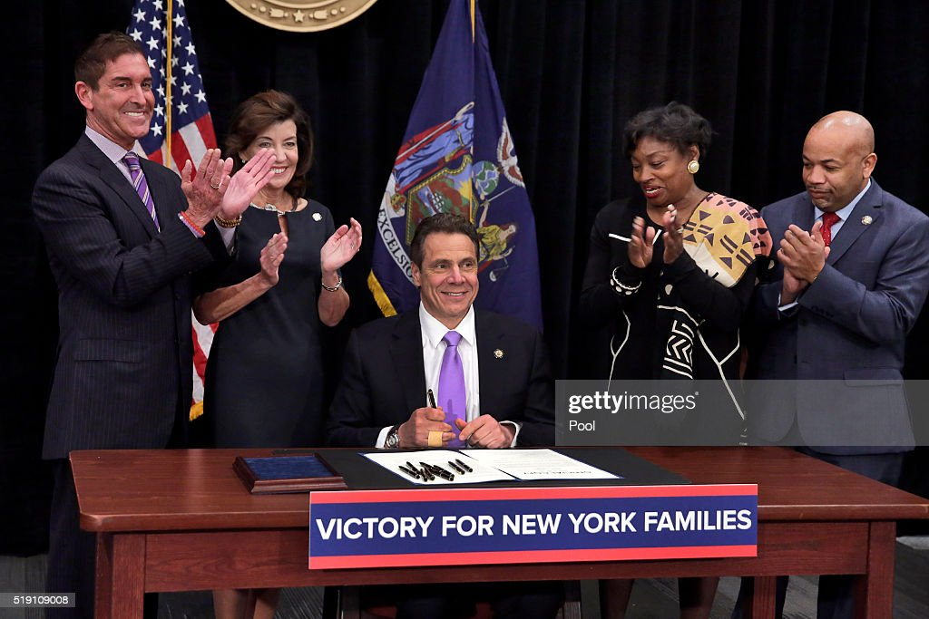 New York Gov Andrew Cuomo center is applauded after he signed a law that will gradually raise New York's minimum wage to $15 at the Javits Convention...